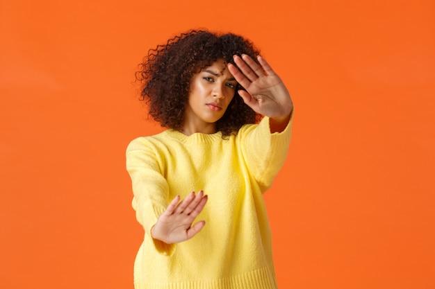 Sin parar, apague las luces. disgustado gruñón linda mujer afroamericana con cara de corte de pelo afro desde el centro de atención, defendiéndose de la luz resplandeciente, de pie naranja reacio