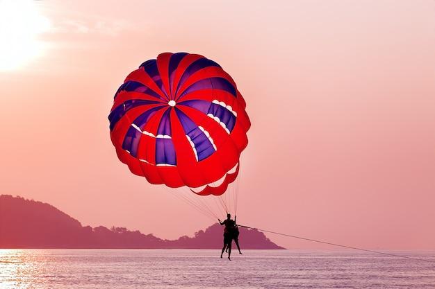 Parasailing durante la puesta de sol en el mar.