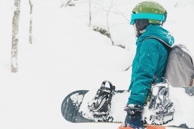 Parasitario caminando con snowboard en invierno