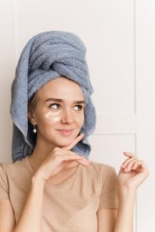 Parche para el área debajo de los ojos. cuidado facial de la piel. una joven mira su piel. sorprendido y divertido rostro de una niña durante una rutina matutina