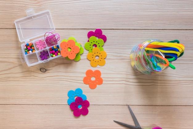 Parche de flores de colores; tallos de chenilla; y caja de perlas sobre fondo de madera