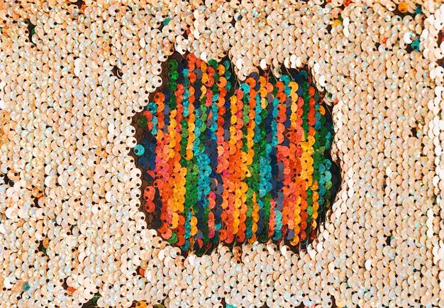 Parche multicolor de lentejuelas rodeado de lentejuelas doradas.