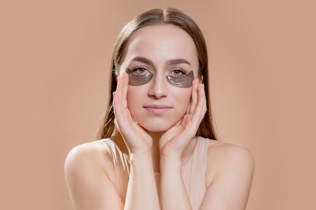 Parche de ojo, hermosa mujer con maquillaje natural y parches de ojo de gel de hidro negro en la piel del rostro.