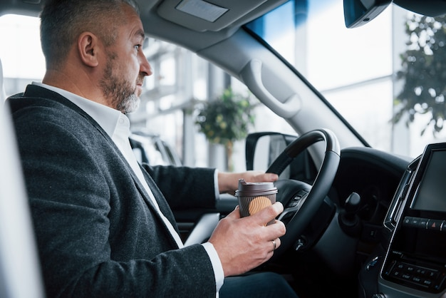 Paré por un descanso. vista lateral del empresario senior en ropa oficial dentro del automóvil moderno