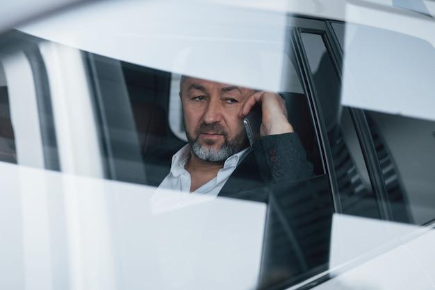 Parece cansado reflexión sobre la ventana. tener una llamada de negocios mientras está sentado en la parte trasera del automóvil de lujo moderno