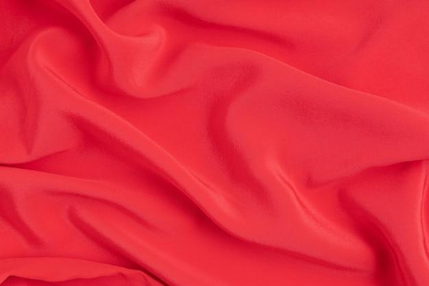 Pared abstracta de tela de seda roja. textura, lujo, moda, idea de estilo.