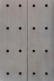 Pared de acero abstracto con agujeros cuadrados
