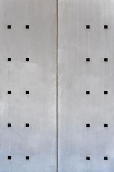Pared de acero abstracto con vista frontal de agujeros cuadrados
