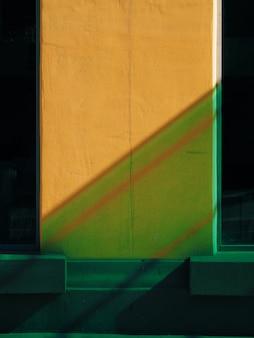 Pared amarilla entre dos ventanas con sombra verde diagonal closeup
