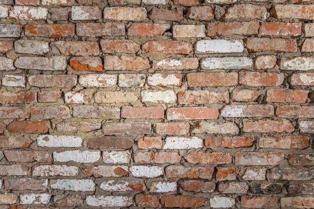 Pared de un antiguo edificio de ladrillo con yeso pelado y superficie pintada.