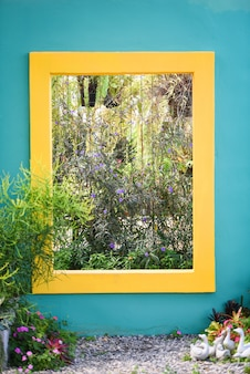 Pared azul con cuadrado amarillo con plantas ornamentales, decoración de jardines y flores.