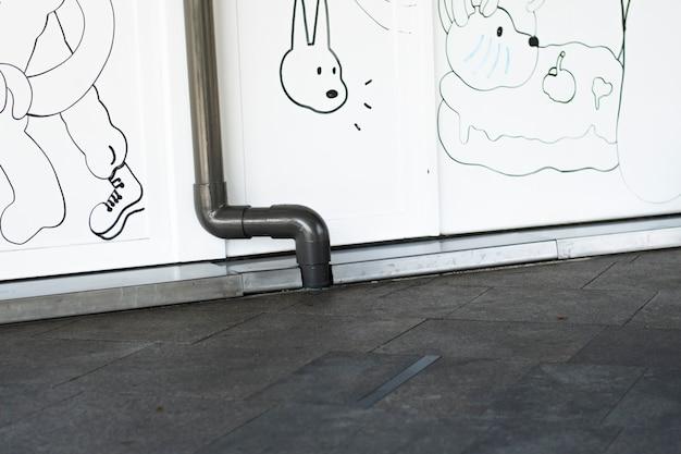 La pared blanca tiene un patrón de dibujos animados con tubos negros instalados en ella.