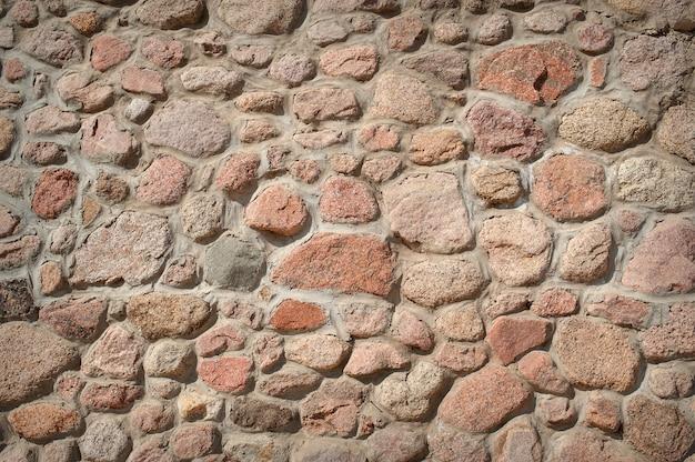 Pared de una casa hecha de piedras de diferentes formas y tamaños.
