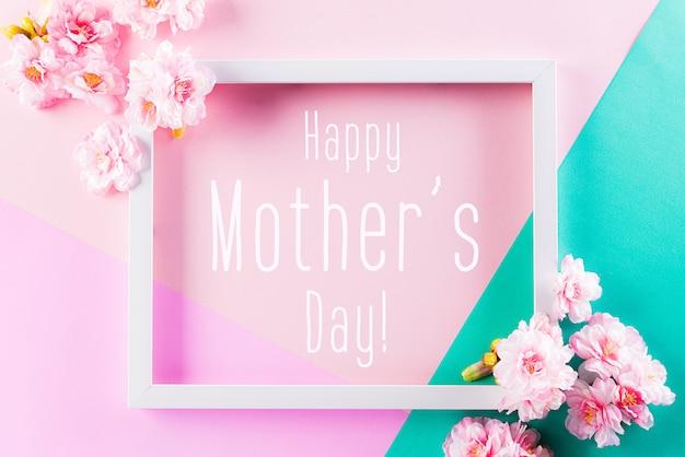 Pared de colores rosa y verde con marco y flores en flor
