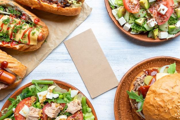 Pared de fotos de alimentos con papel artesanal en blanco. composición con hot dogs, hamburguesas y ensaladas. gran imagen para el diseño de comida callejera. copia espacio
