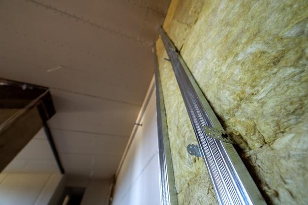 Pared de una habitación en proceso de renovación con aislamiento de lana mineral de roca y estructura de metal preparada para placas de paneles de yeso.