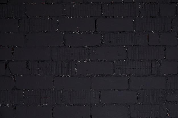 Pared de ladrillo negro irregular con cemento negro en huecos