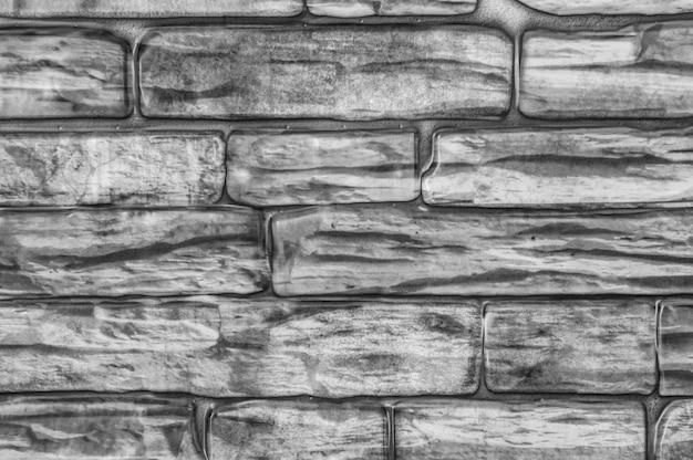 Pared de ladrillos de diferentes formas de primer plano en blanco y negro.