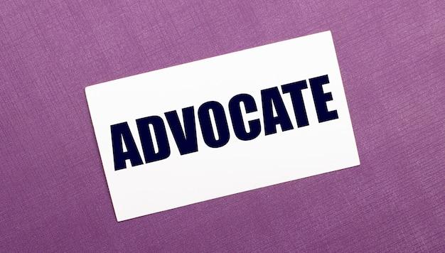 En una pared lila, una tarjeta blanca con la palabra advocate