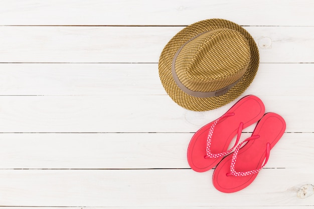 Pared de madera blanca con sombrero de paja, toalla de playa y chanclas