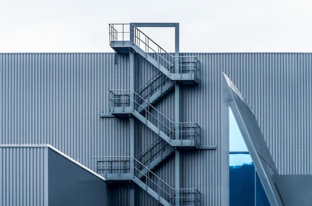 Pared de metal gris con escaleras de caracol bajo el cielo despejado