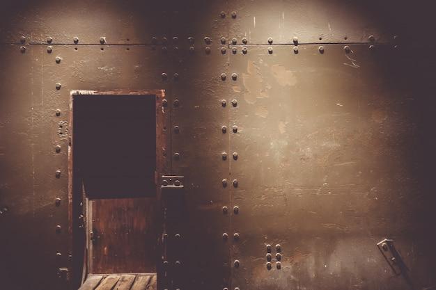 Pared de metal oscuro y puerta en un búnker