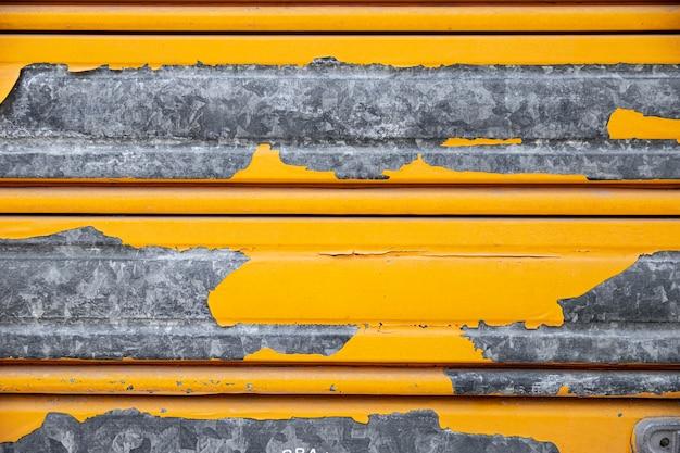Pared metálica oxidada con pintura amarilla