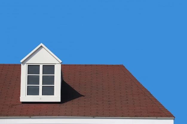 Pared moderna de la casa del diseño del tejado de aguilón con el fondo claro de cielo azul.