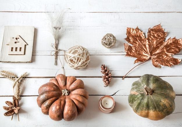 Pared de otoño con diferentes objetos y calabaza. lay-lay.