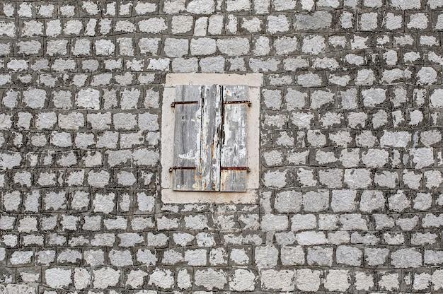 La pared de piedra de la casa vieja, con contraventanas agrietadas en madera clara