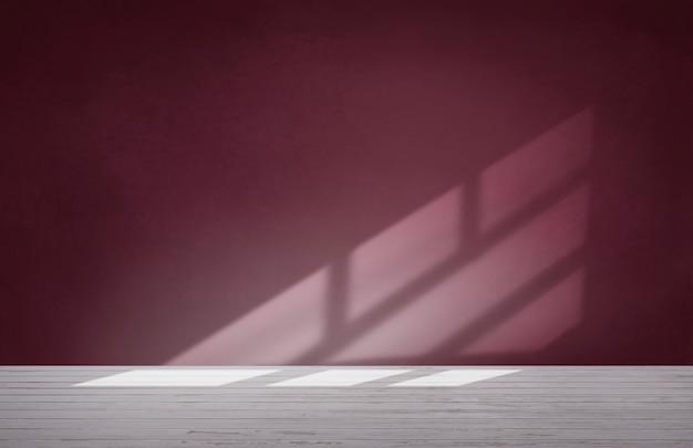 Pared roja borgoña en una habitación vacía con piso de concreto