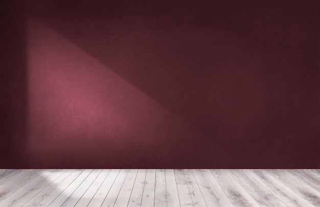 Pared roja borgoña en una habitación vacía con piso de madera