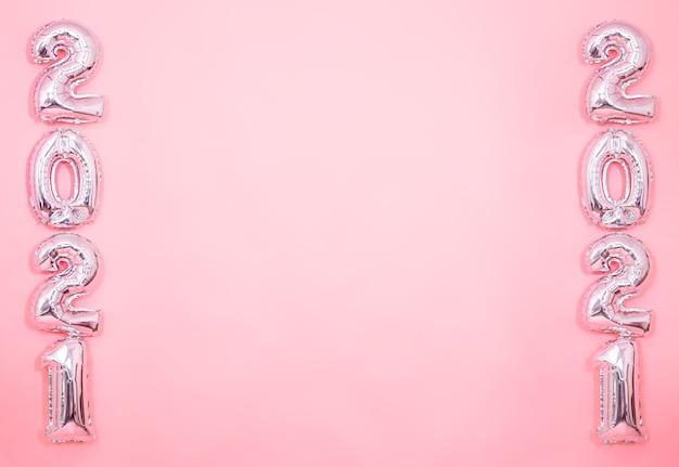 Pared rosa claro con globos plateados de año nuevo en forma de números en ambos lados, fondo de año nuevo