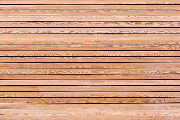 Una pared sólida de tablones de madera marrón dispuestos horizontalmente. concepto de textura, interior