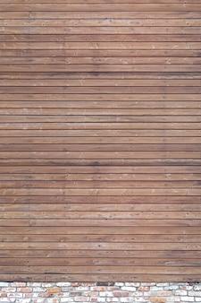 Una pared sólida de tablones de madera marrón envejecida con clavos martillados ubicados horizontalmente sobre una base de ladrillo.