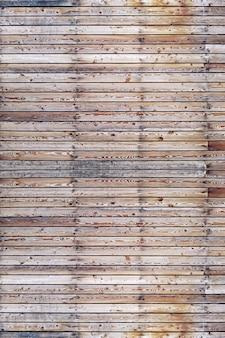 Una pared sólida de tablones de madera marrón envejecida con clavos martillados ubicados horizontalmente.