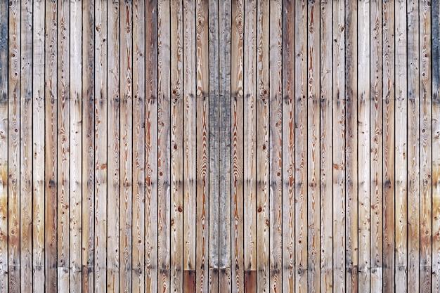 Una pared sólida de tablones de madera marrón envejecida con clavos obstruidos ubicados verticalmente.