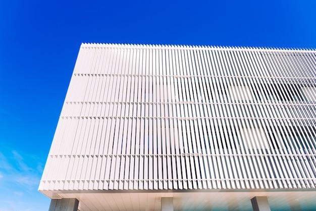 Pared con tableros de metal blanco y cielo azul.
