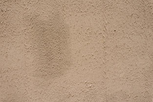 Pared con textura beige, fondo. yeso estructural recubierto con pintura acrílica a base de agua. superficie rugosa y desigual de color beige. copia espacio