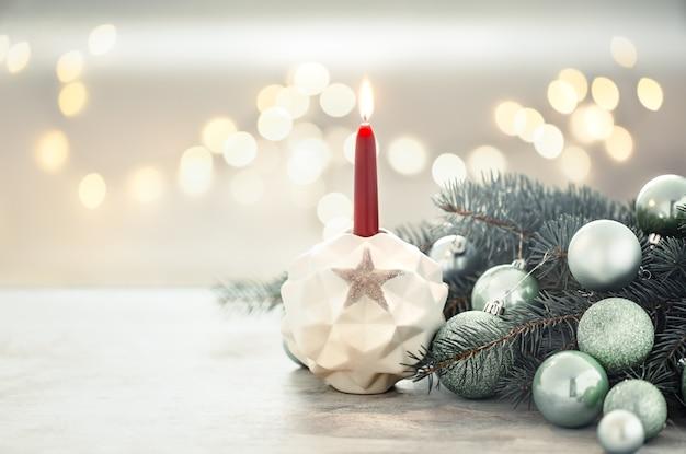 Pared de vacaciones de navidad con una vela en un candelero.