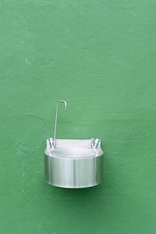 Pared verde con fuente metálica en cancha de tenis