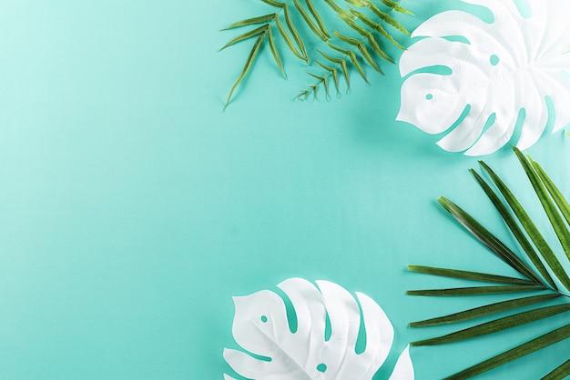Pared verde tropical de verano con hojas de palma y monstera.