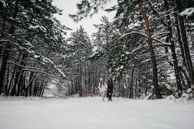 Una pareja se abraza en un bosque nevado contra árboles