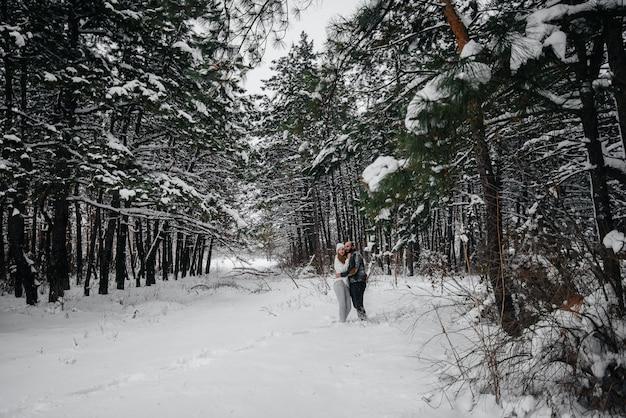 Una pareja se abraza en un bosque nevado