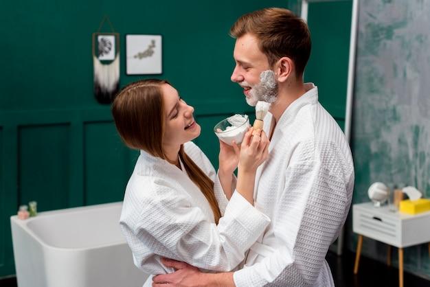 Pareja abrazada en batas de baño aplicando espuma de afeitar