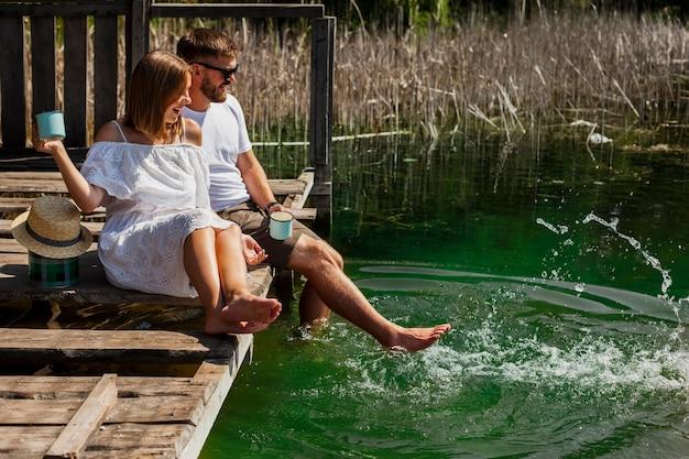 Pareja abrazada jugando con los pies en el agua