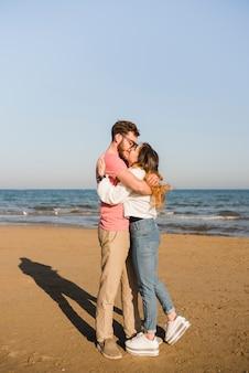 Pareja abrazándose besándose cerca de la orilla del mar en la playa