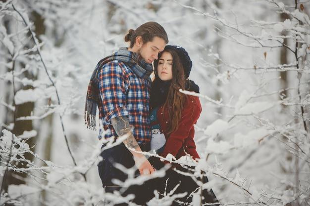 Pareja abrazándose en el bosque de invierno
