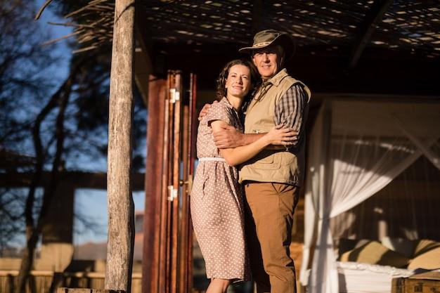 Pareja abrazándose en cabaña durante vacaciones de safari