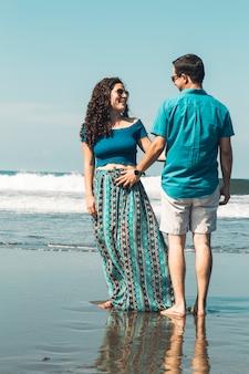 Pareja abrazándose por la cintura de pie en la playa